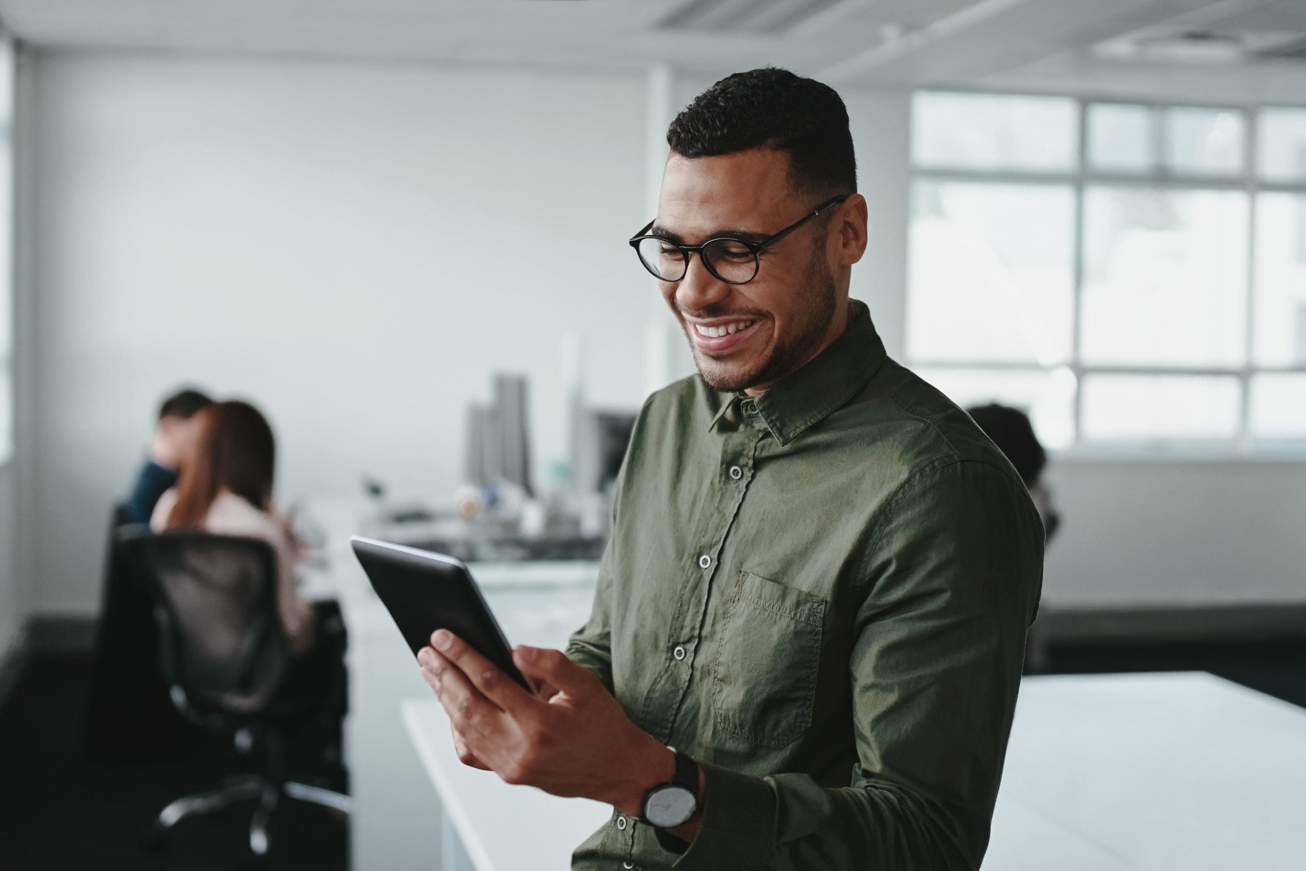Smiling young businessman touching smartphone and checking online information in the modern office
