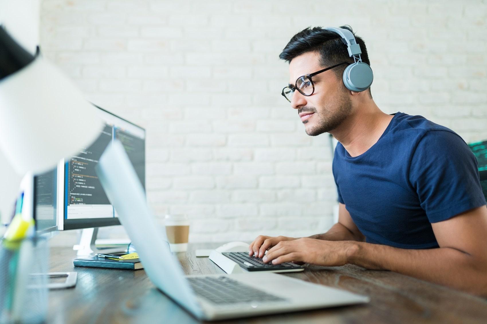 Software developer programming at desk, wearing headphones
