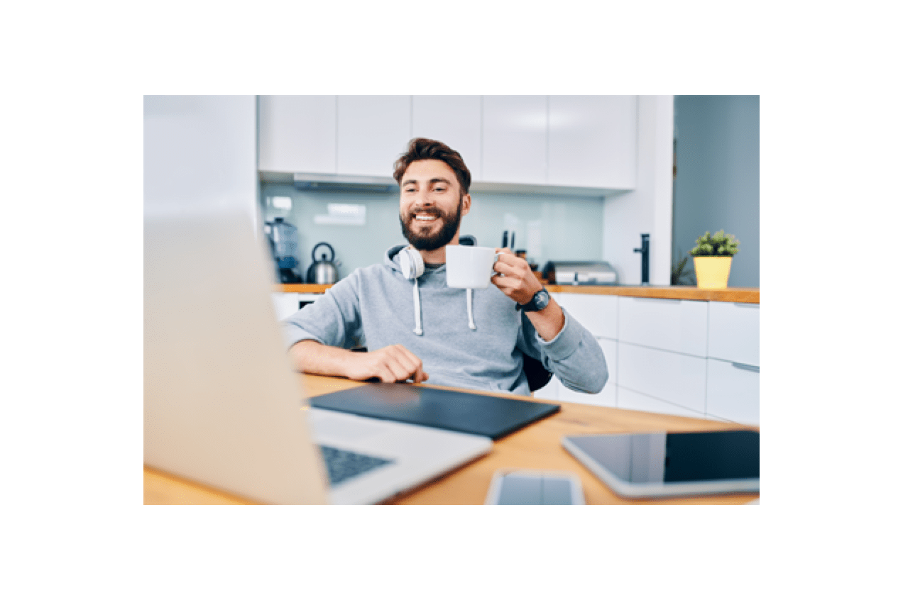 Young man holding a cup of coffee smiling while seated at his home office desk