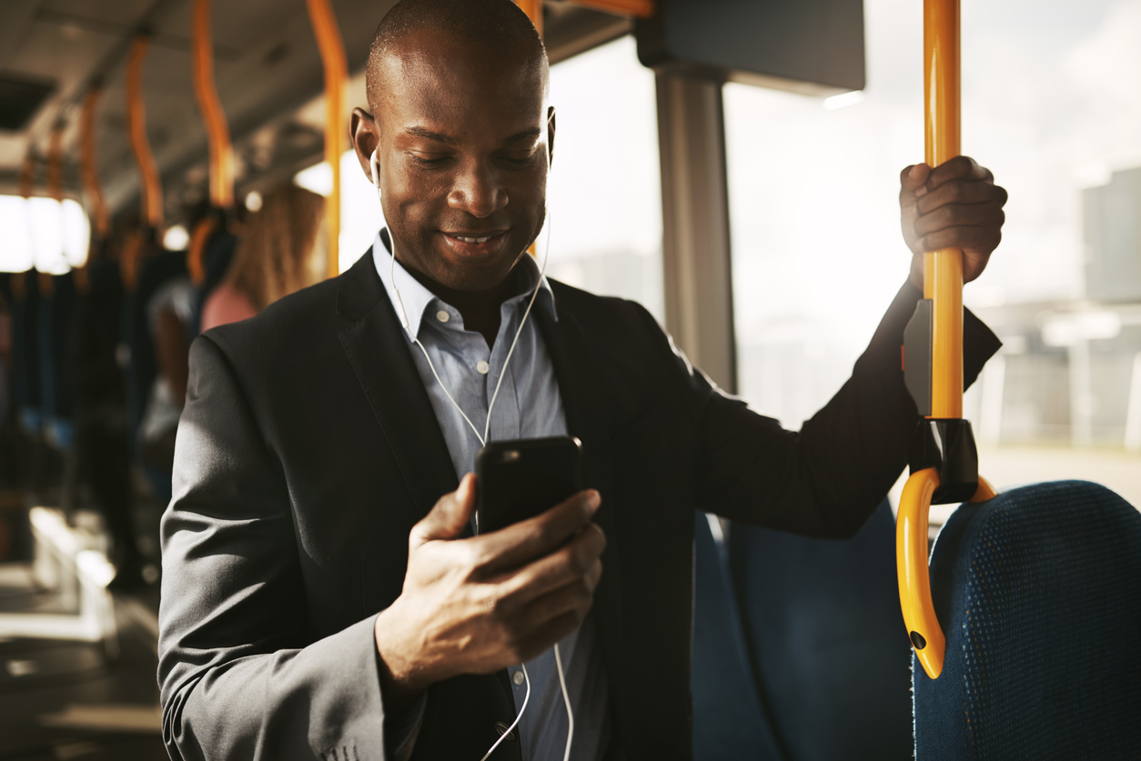 Recruiter checks for updates on their mobile device while commuting on a train